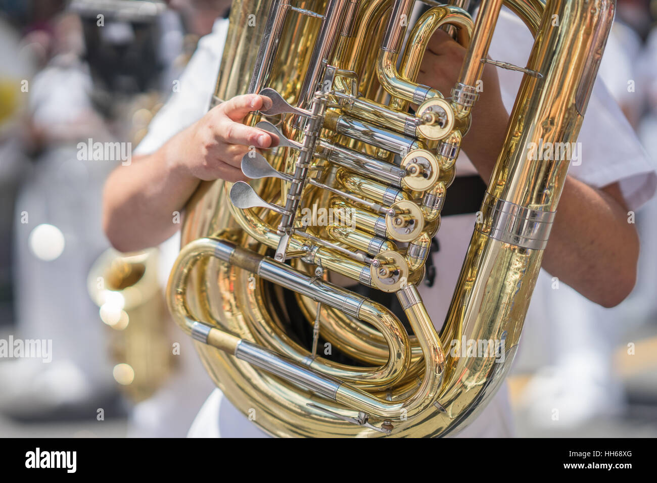 Tuba player in a military or marching band playing during a parade or festival on a sunny day. Wearing a white uniform Stock Photo