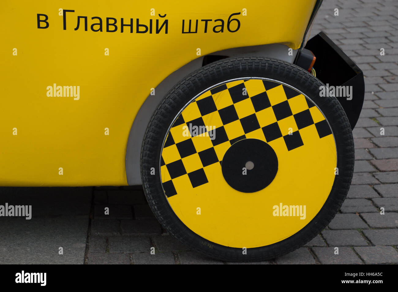 Close up of yellow and black checkerboard wheel on a taxi with Russian phrase on rear fender. Cab is parked on brick - Stock Image