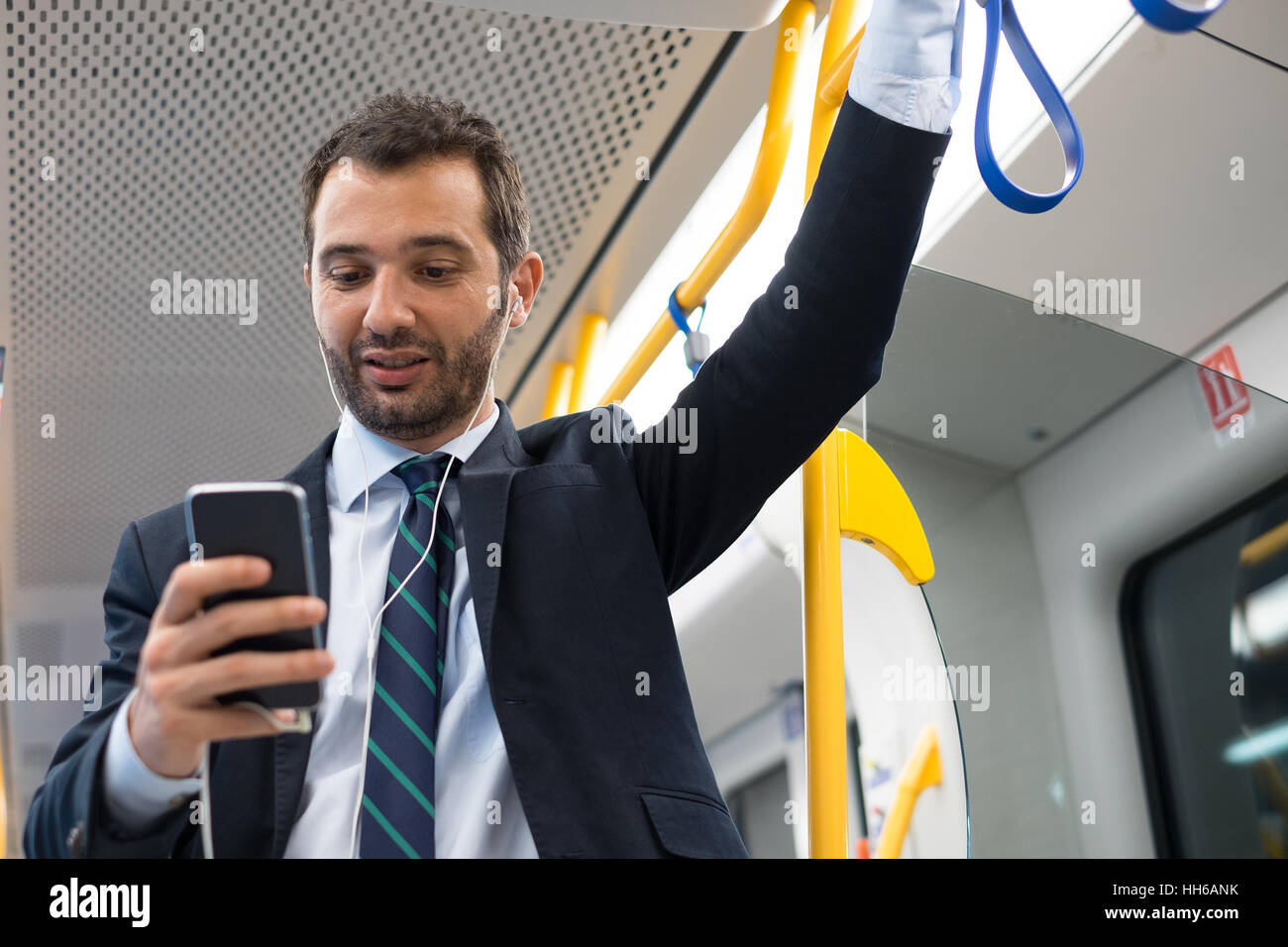 Businessman commuter traveling on the metro underground - Stock Image