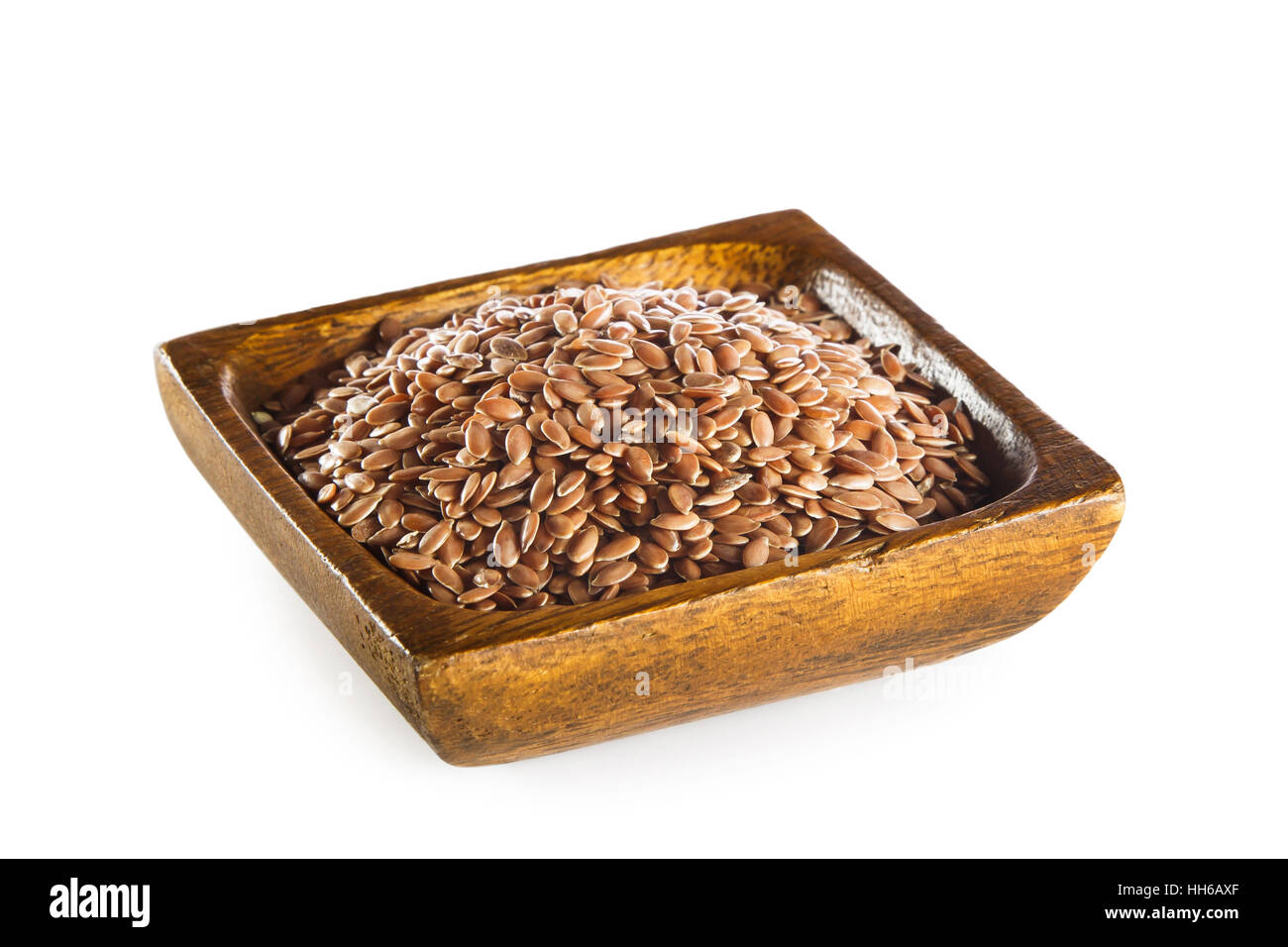 Linseed in wooden bowl isolated on white background - Stock Image