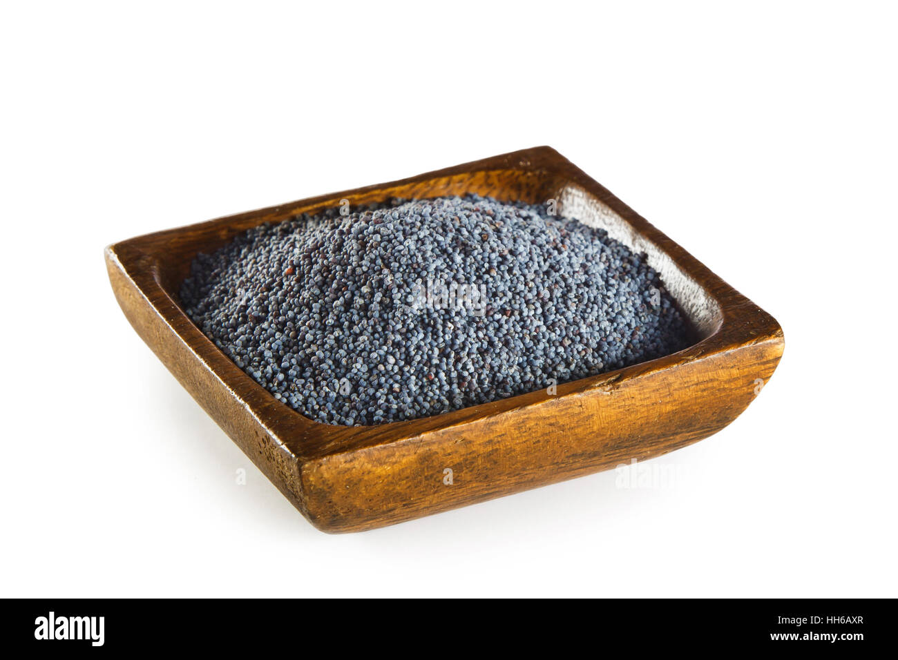 Blue poppy seeds in wooden bowl isolated on white background - Stock Image