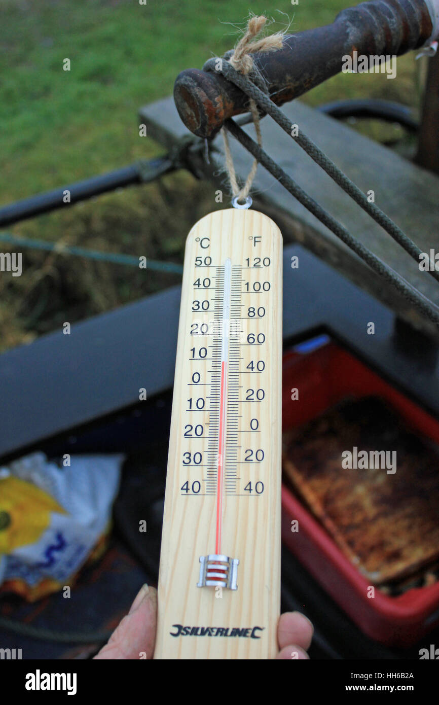 A thermometer mounted on a wooden base being used to take and record the outdoor temperature in connection with - Stock Image