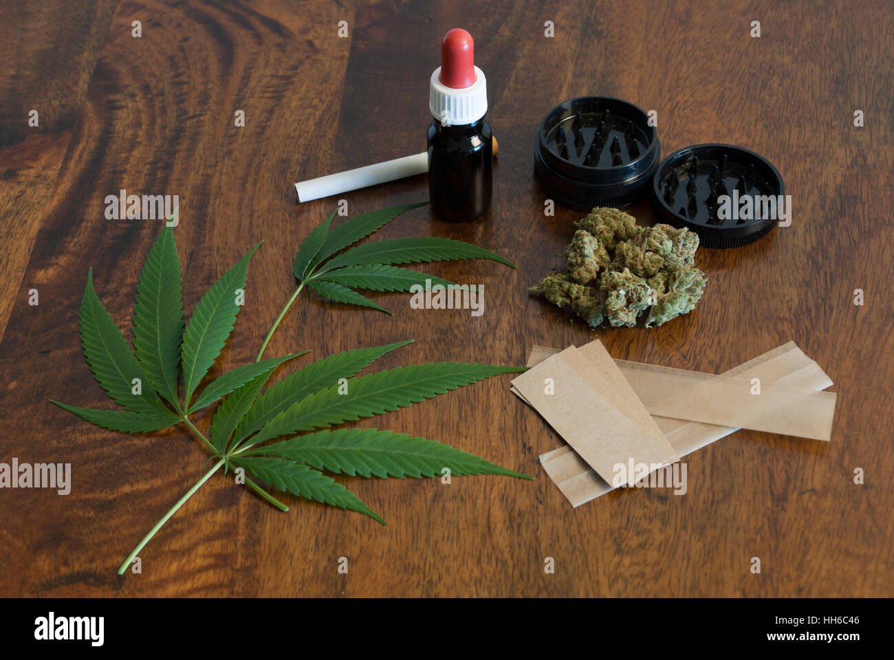 Cannabis sativa weed leafs and flower buds on wooden background with grinder and large smoking paper Stock Photo