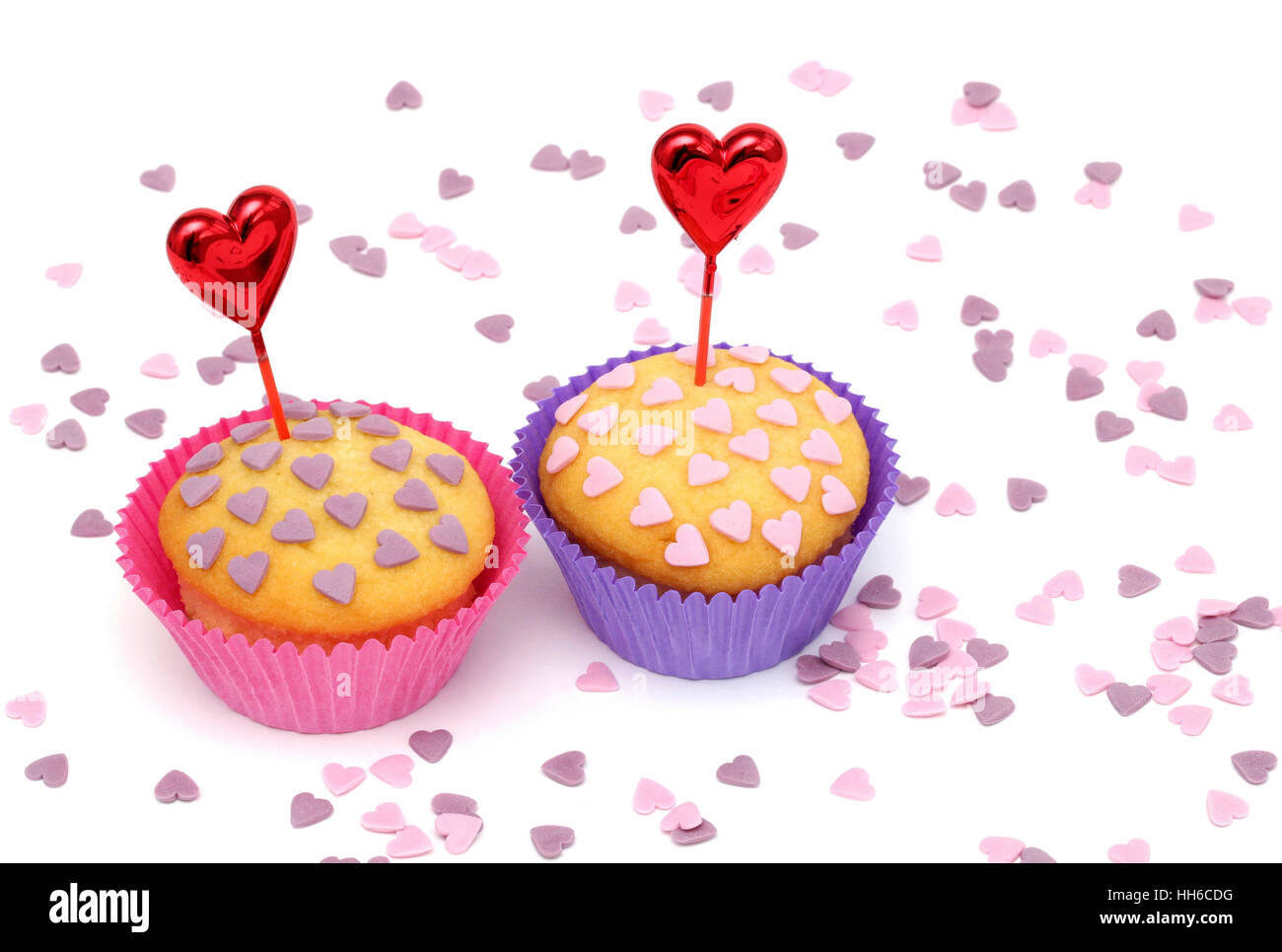 Two cupcakes with little pink and purple hearts - Stock Image