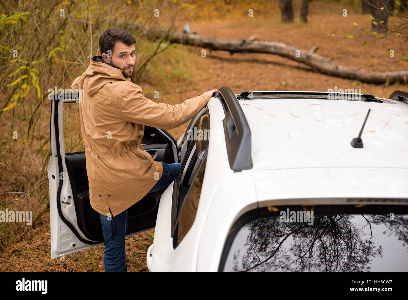 Young man standing near white car and big fallen tree on forest road at autumn day Stock Photo