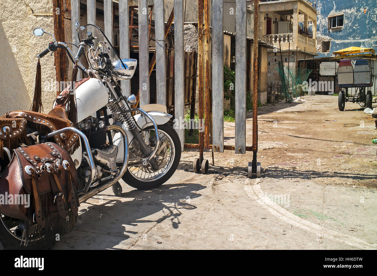 motorbike with leather sadle bags leather helmet outside rickshaw garage Havana Cuba - Stock Image