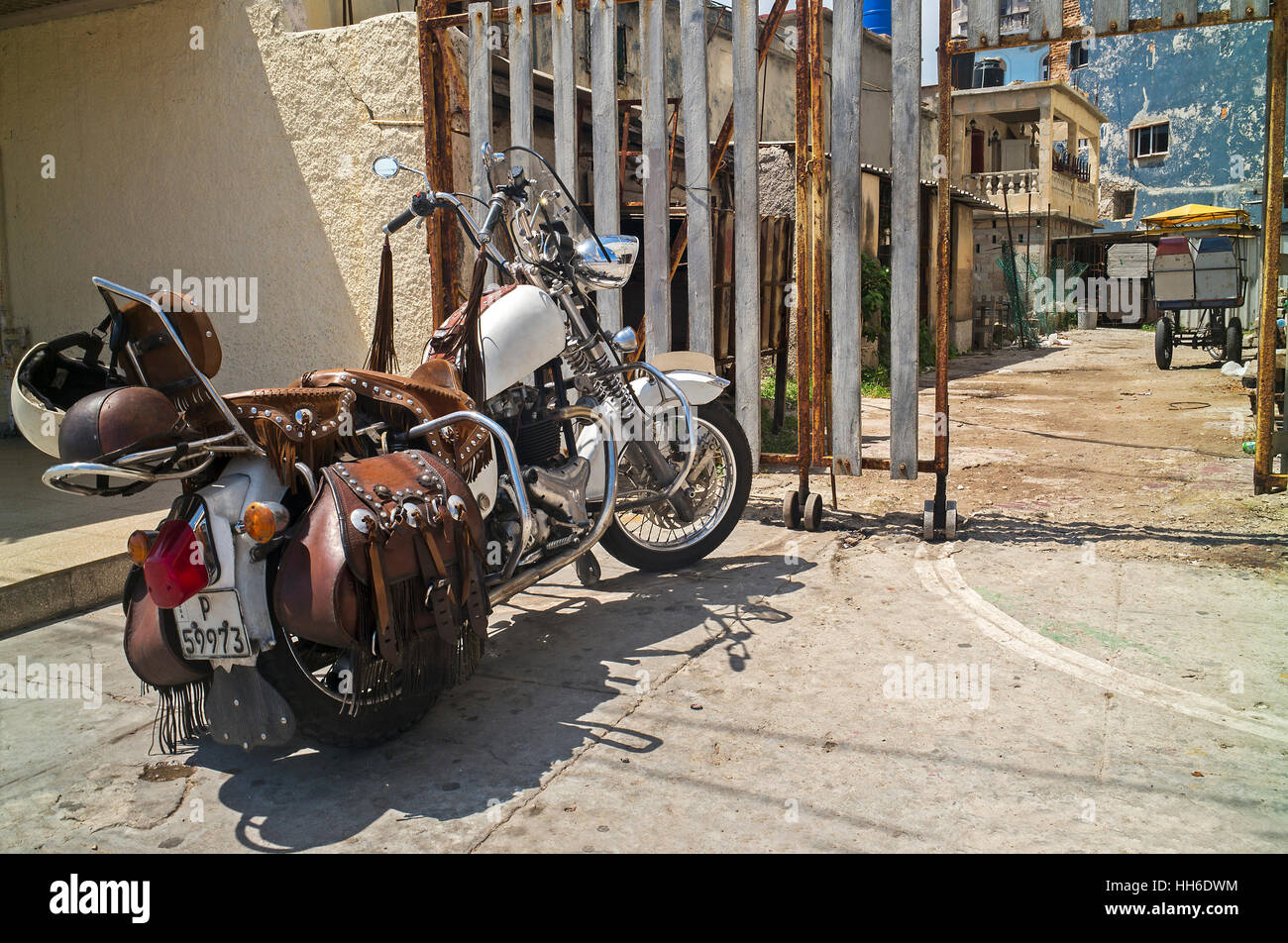 white motorbike parked with leather sadle bags and handlebar tassles on a road in Havana Cuba - Stock Image