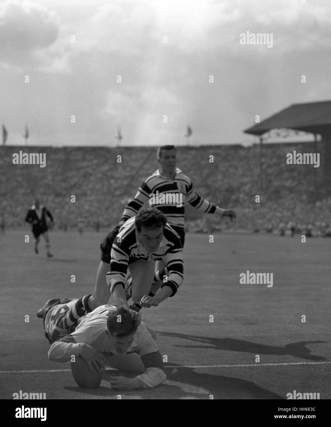 K. Holliday, the Wakefield Trinity half-back, scores the fourth try for his team, as a vain attempt to stop him - Stock Image