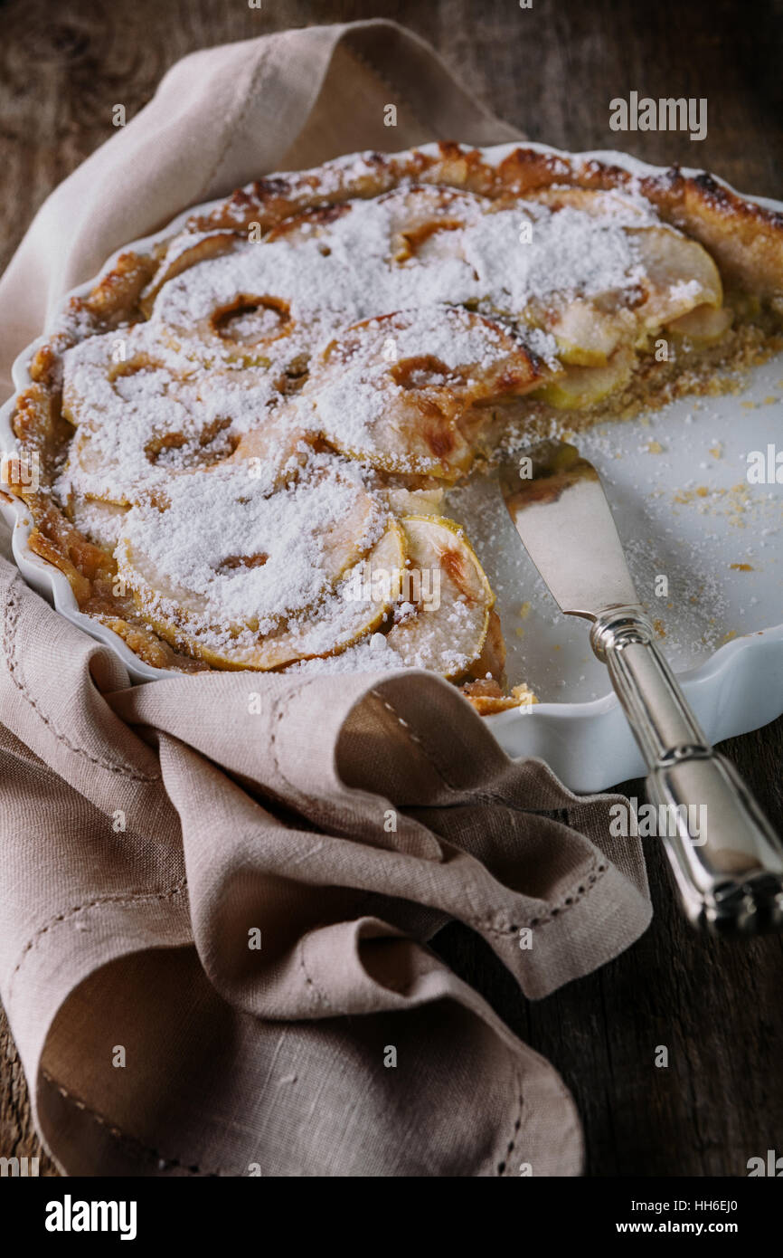 Apple pie with the knife on wooden table - Stock Image