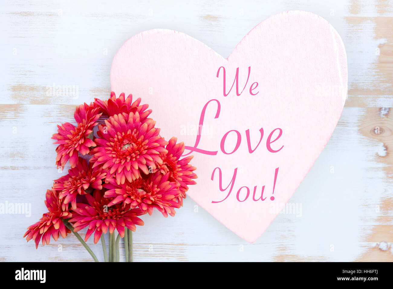 Beautiful Red Flowers And Wooden Heart With Words We Love You Stock