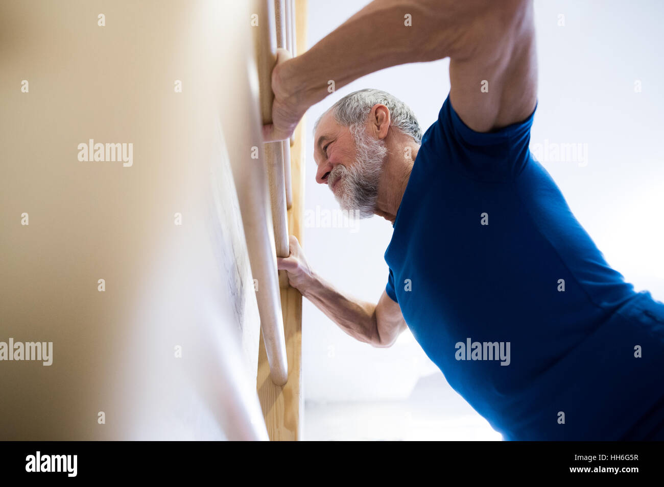 Senior man in gym exercising on wall bars. - Stock Image