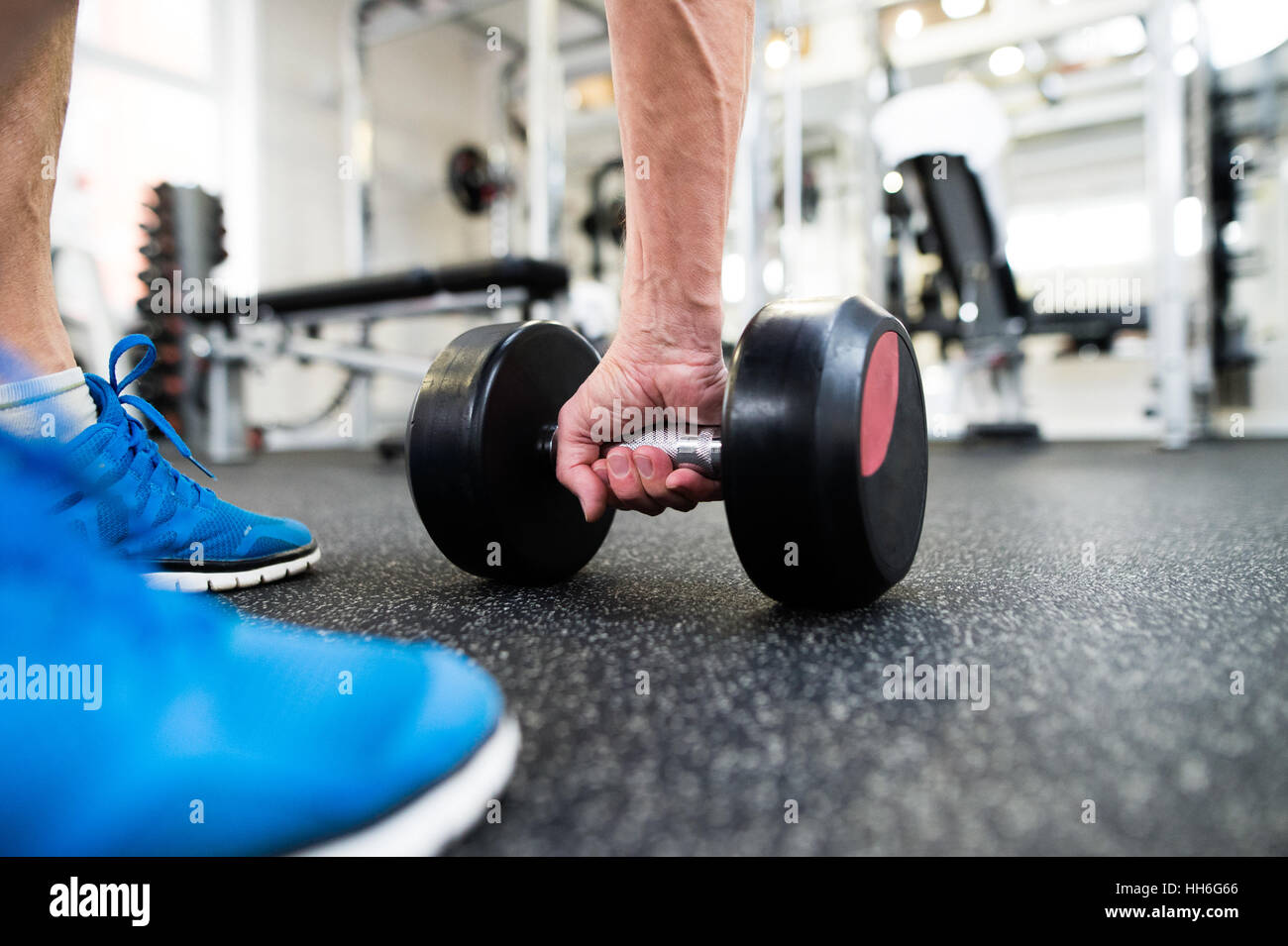 Unrecognizable senior man in gym working out with weights - Stock Image