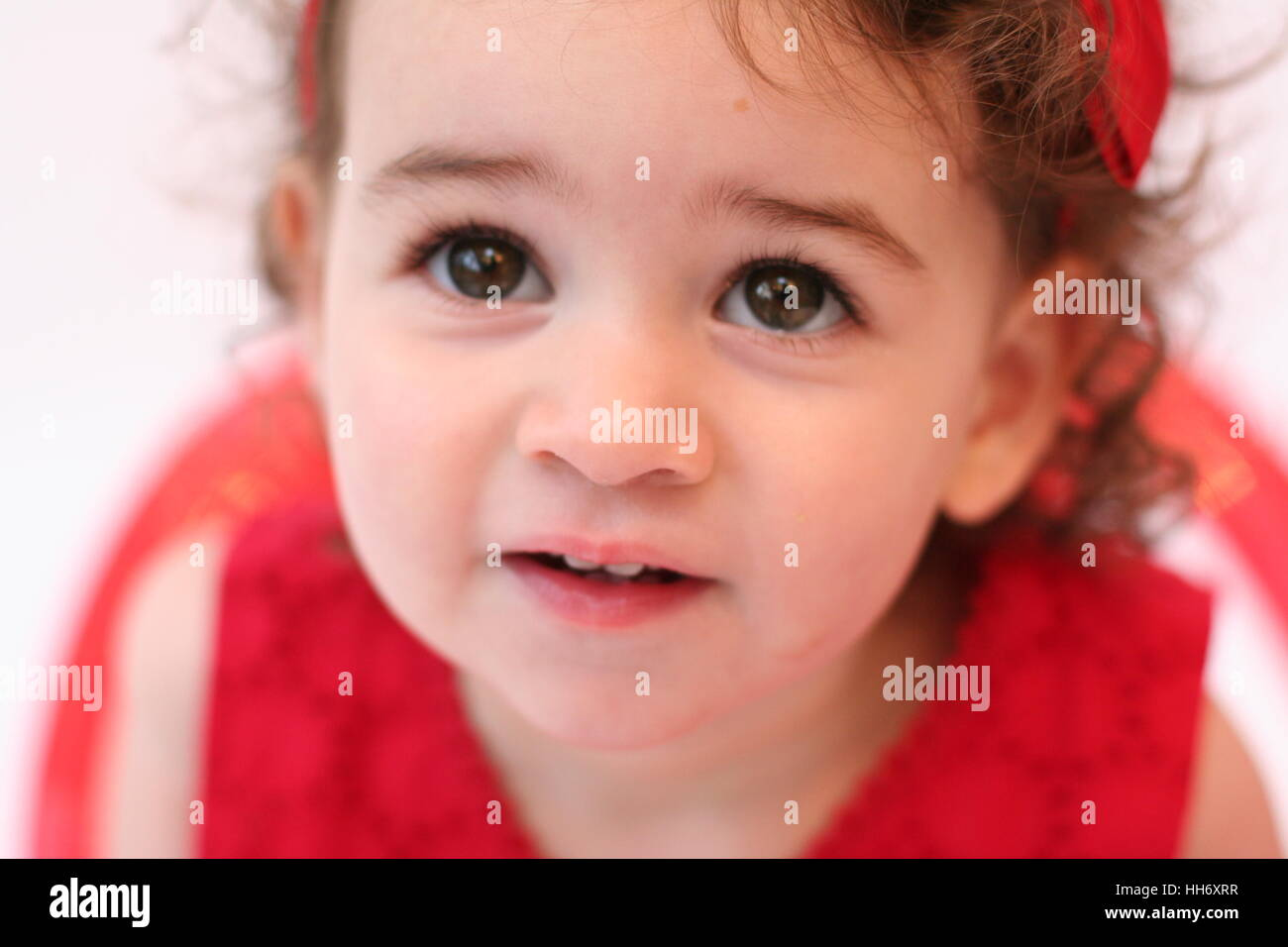close up of a sweet baby girl child kid toddler with curly hair and