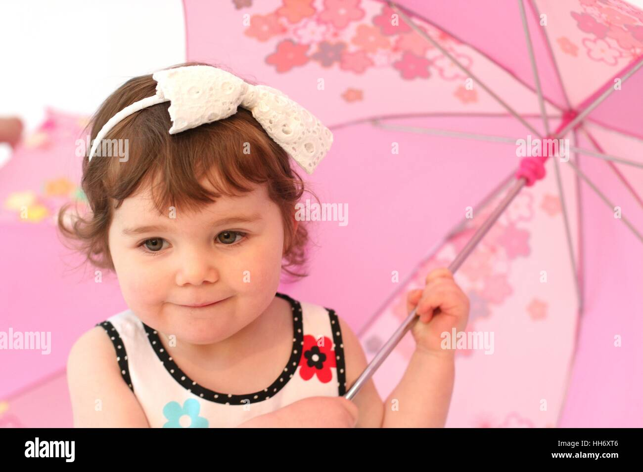 Little girl child playing with a pink umbrella wearing a bow hairband, happy toddler, innocent concept, family fun, - Stock Image