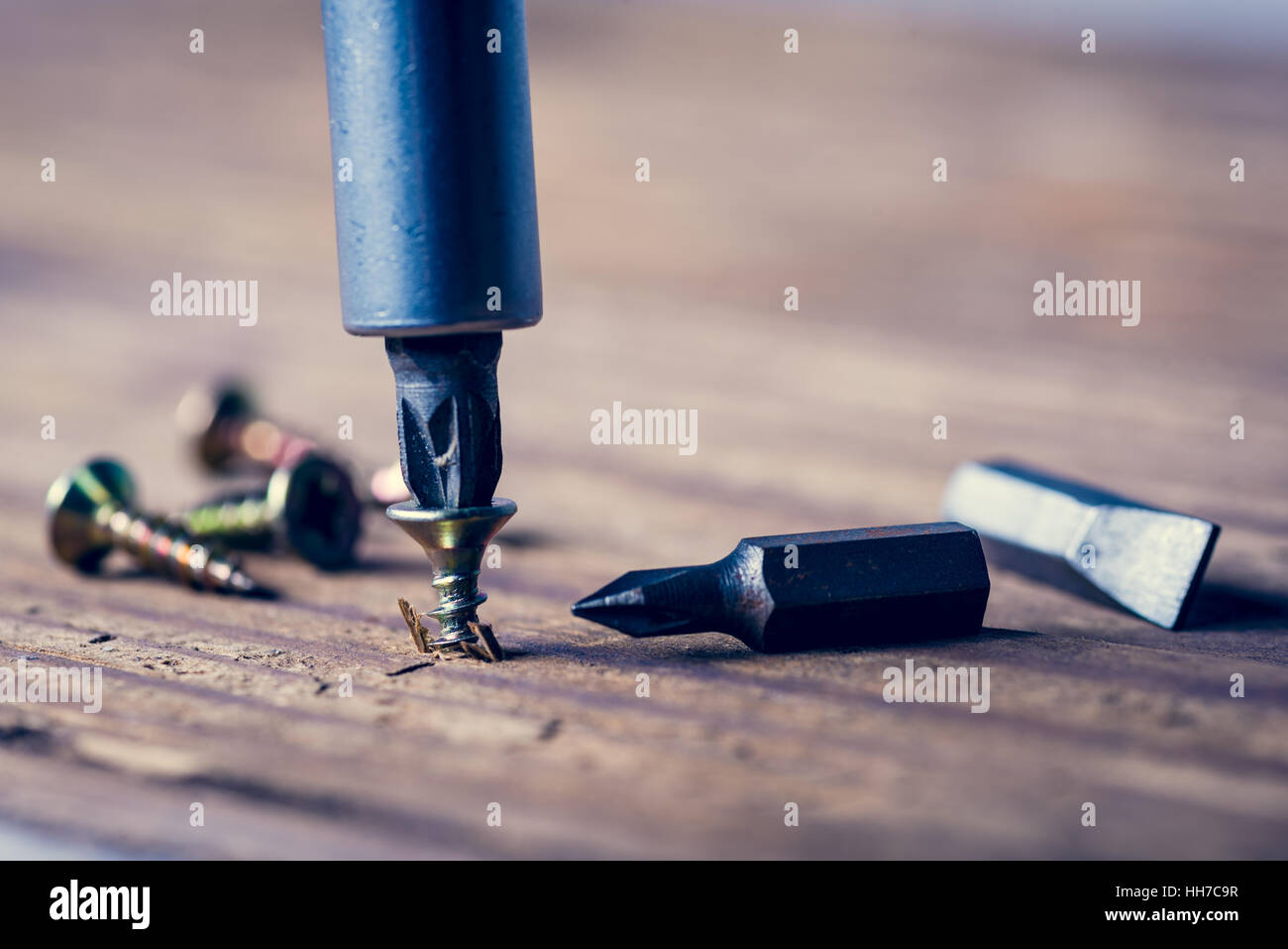 Someone is screwing a screw into wooden surface with the screwdriver. DIY concept. - Stock Image