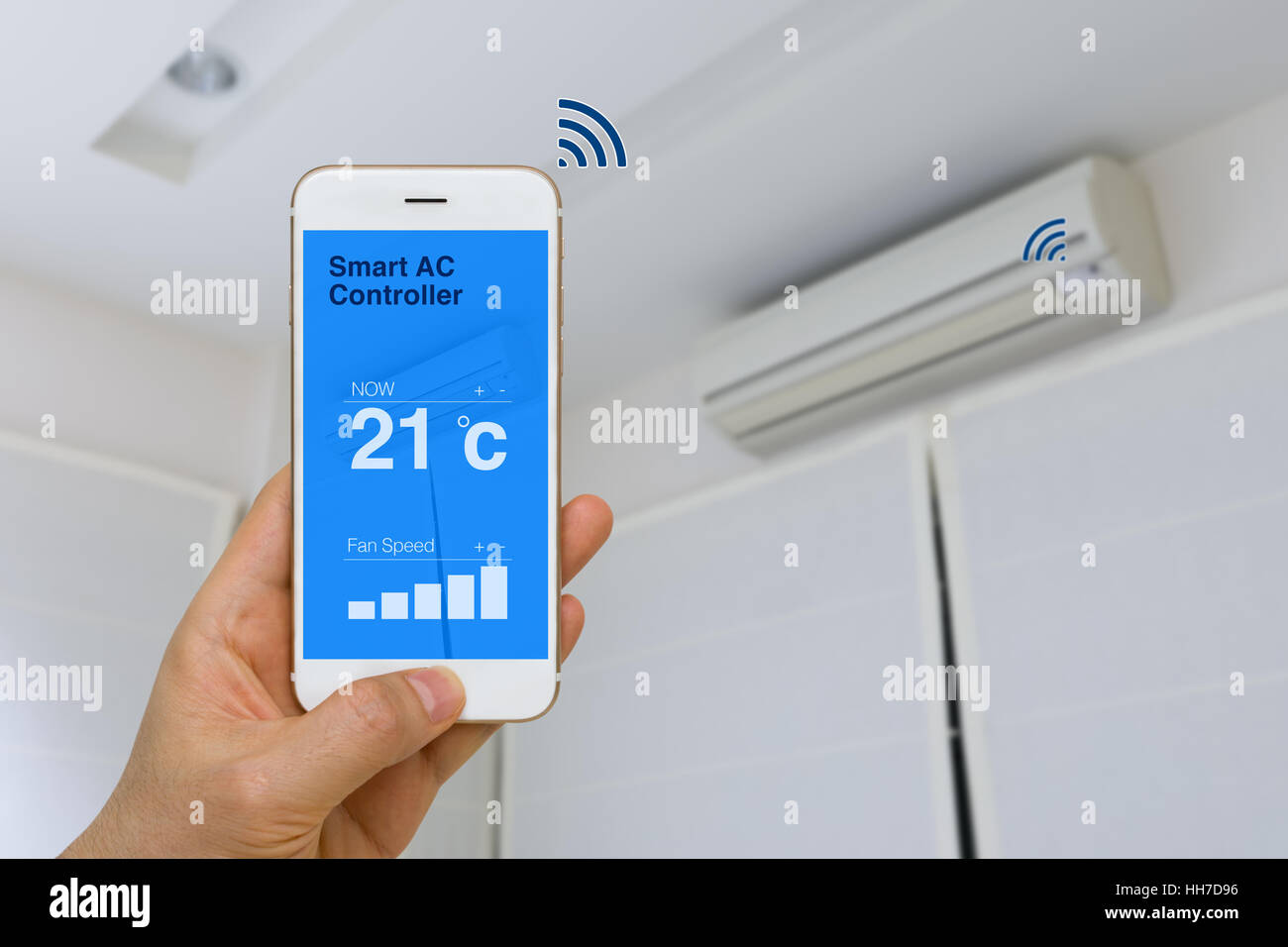 Concept of IOT, remotely controlling smart air conditioner with app on smartphone from distance. - Stock Image