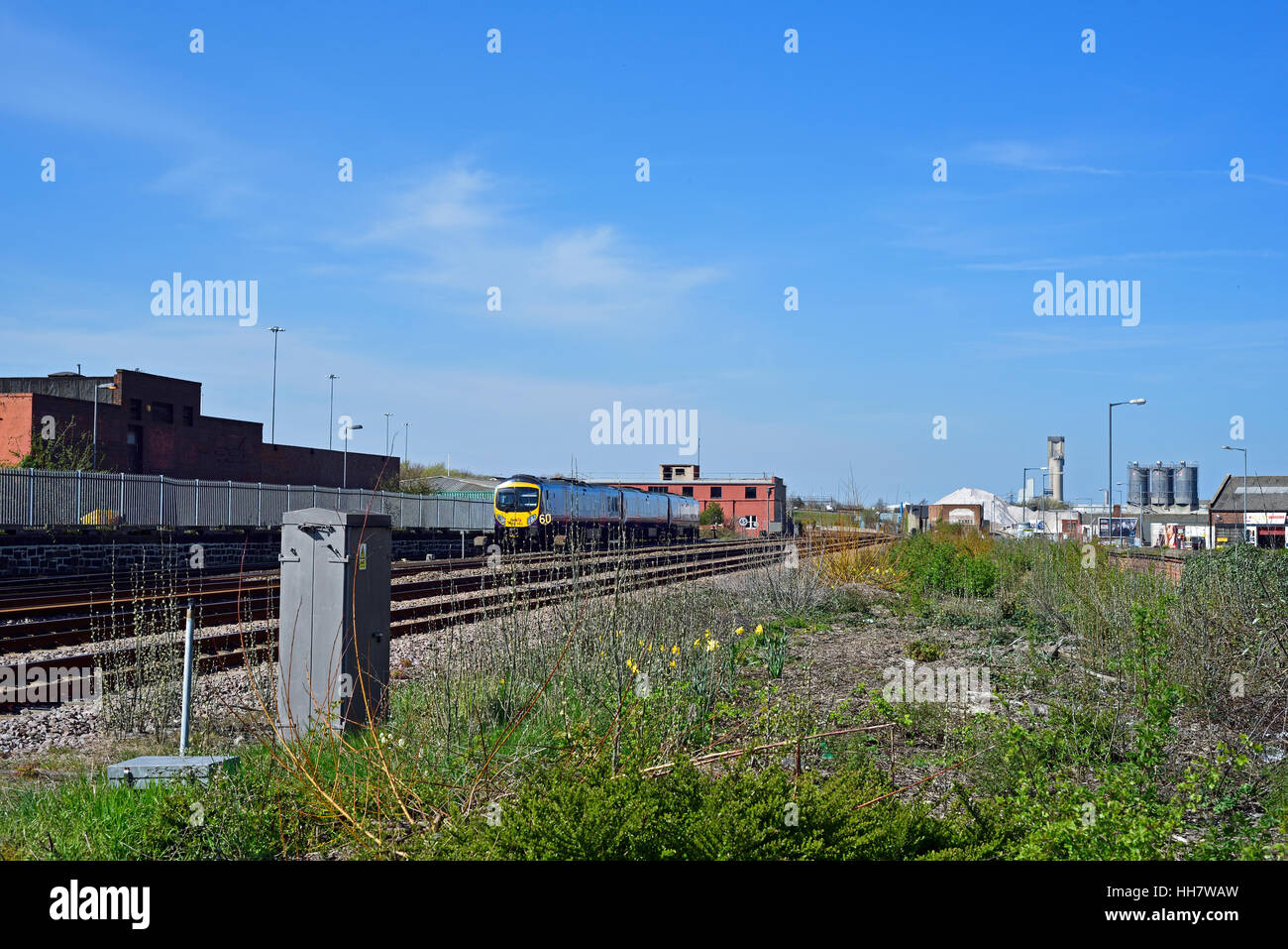 stretch of railway line near Middlesbrough Station with local Northern-Rail train and industrial chemical works - Stock Image