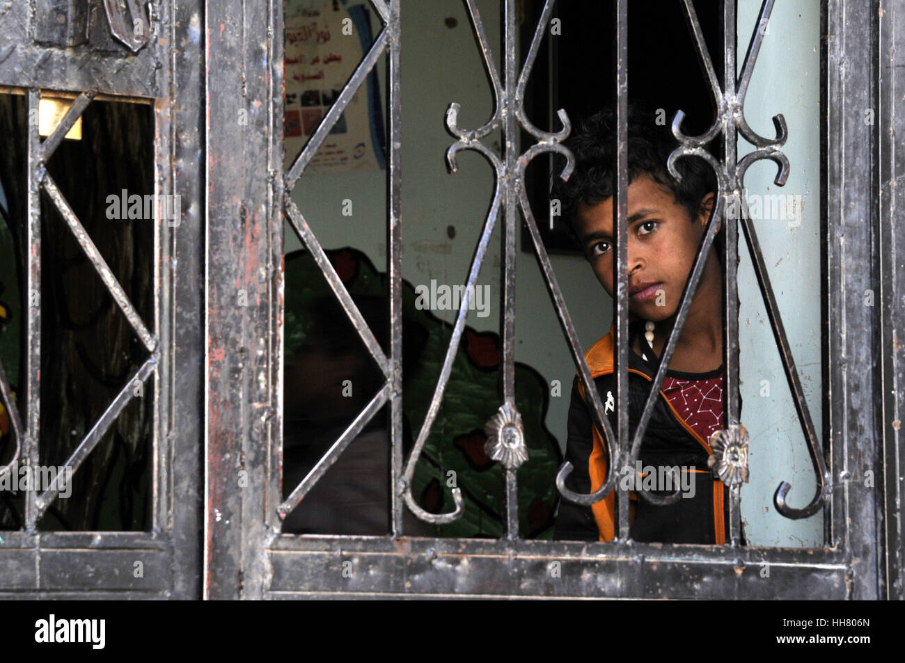 Sanaa, Yemen. 17th Jan, 2017. An orphan looks through his inhabitation gate at the government-run Orphans Institution - Stock Image