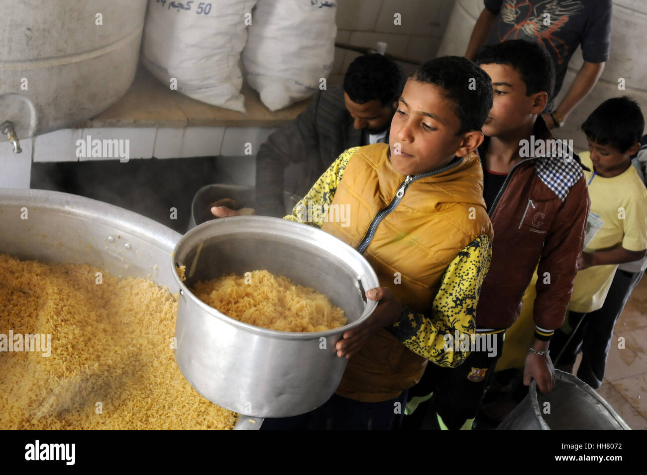 Sanaa, Yemen. 17th Jan, 2017. Orphans stand carrying their meal cans at the restaurant of the government-run Orphans - Stock Image