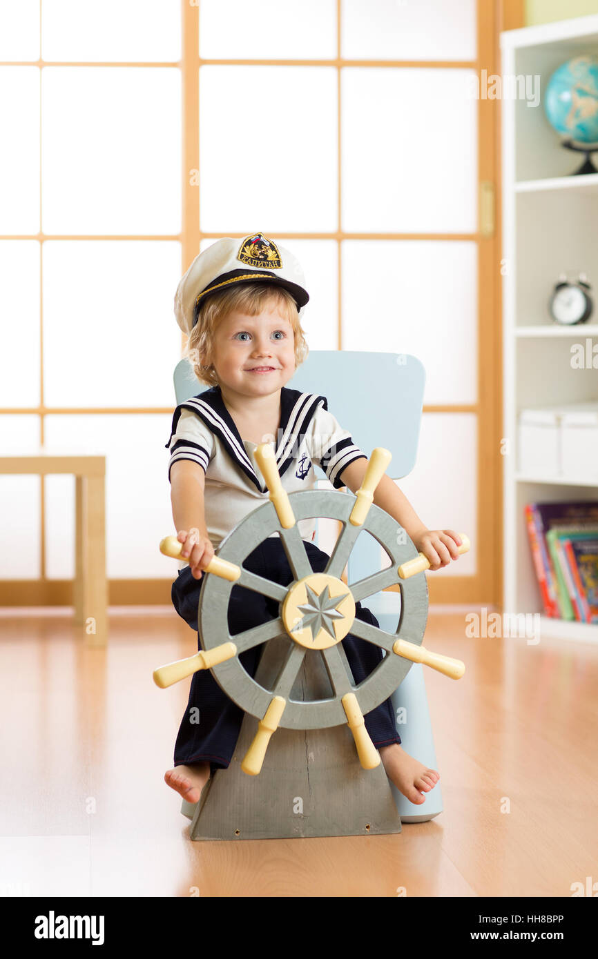 Kid dressed as a captain or sailor plays on chair as on ship in his room. Child boy rotates the wooden steering Stock Photo