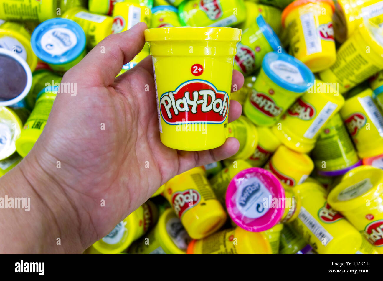 Paphos, Cyprus - October 18, 2016 Woman hand with Play-Doh can against heap of Play-Doh containers with different - Stock Image