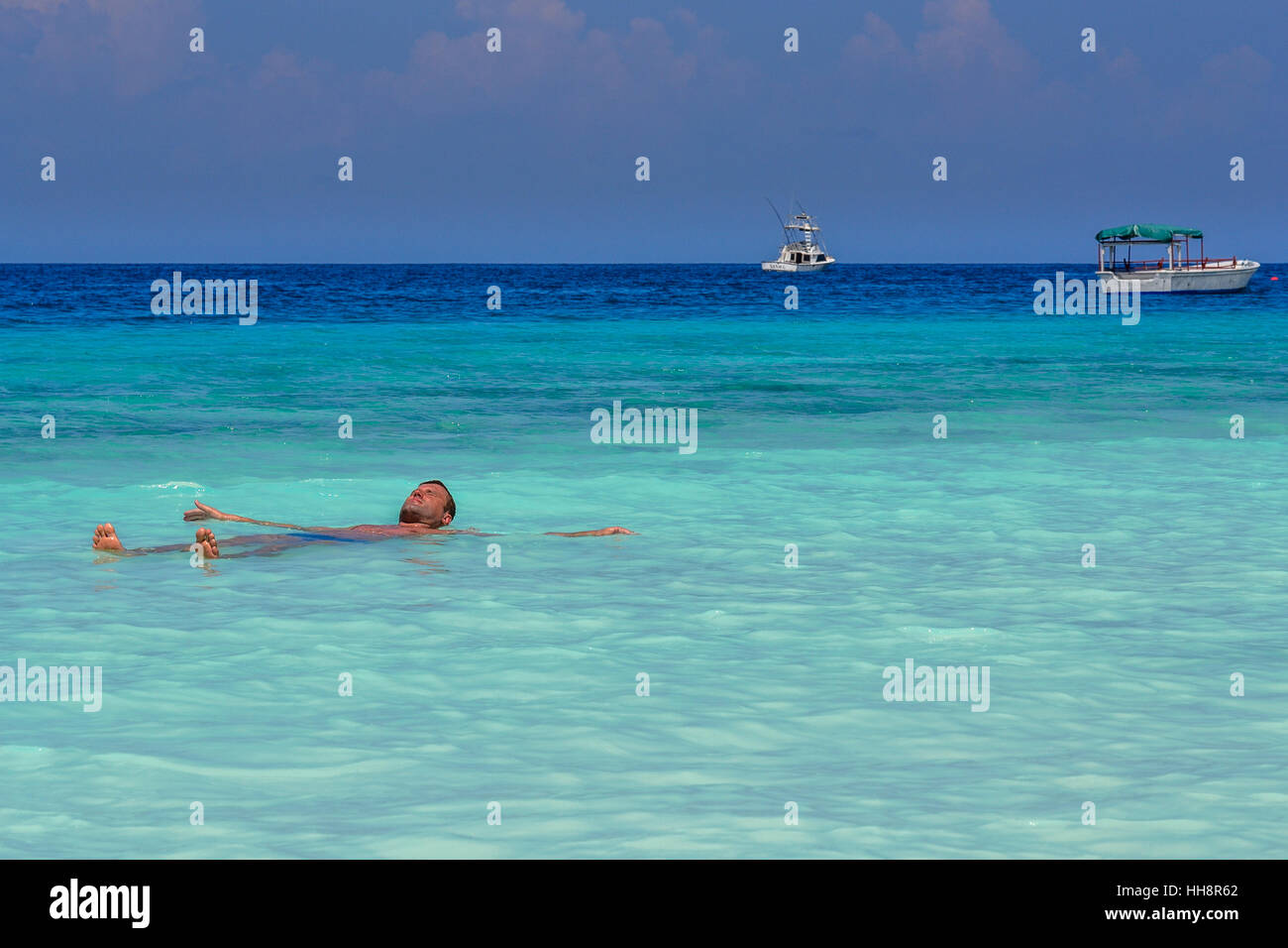Man is relaxing in paradise beach and blue water,Zanzibar - Stock Image