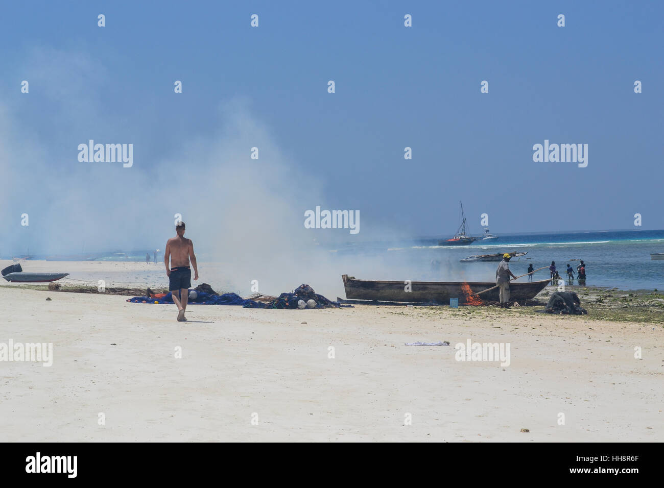 man is walking next boat burning in Nungwi beach - Stock Image