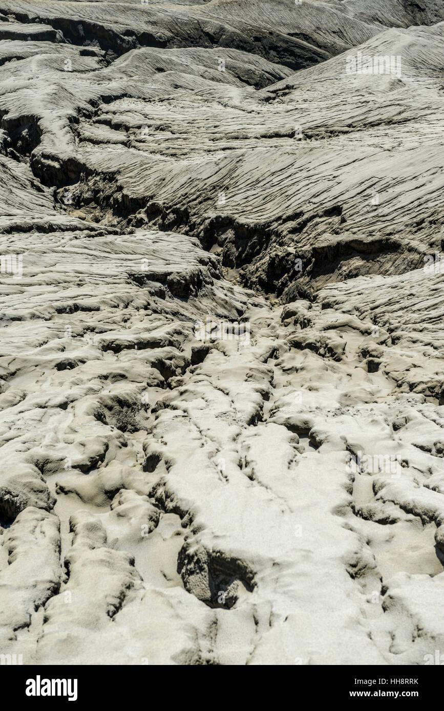 Hostile volcanic landscape, gaps and cracks, dry ground on volcano crater, Mount Bromo, Bromo Tengger Semeru National - Stock Image