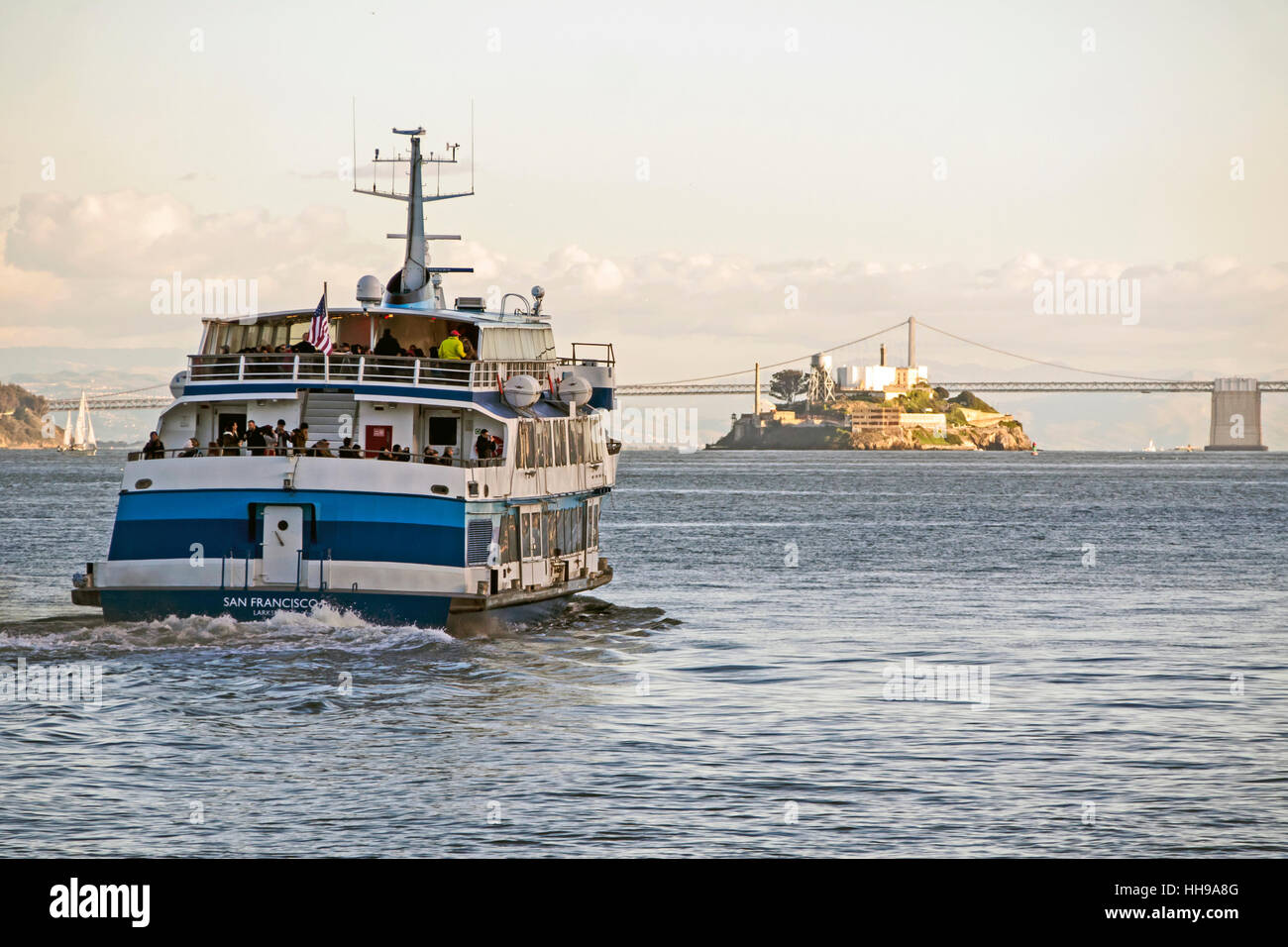 Late afternoon ferry leaving Sausalito for San Francisco with Alcatraz island and the Bay Bridge in the background, - Stock Image