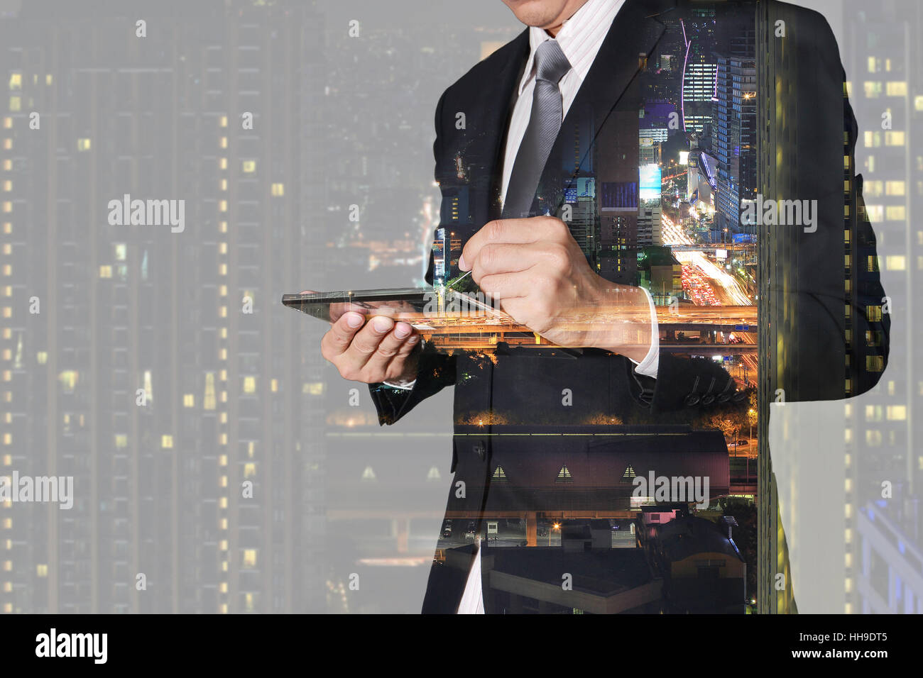 Double exposure of businessman working with tablet,  night city and night street - Stock Image