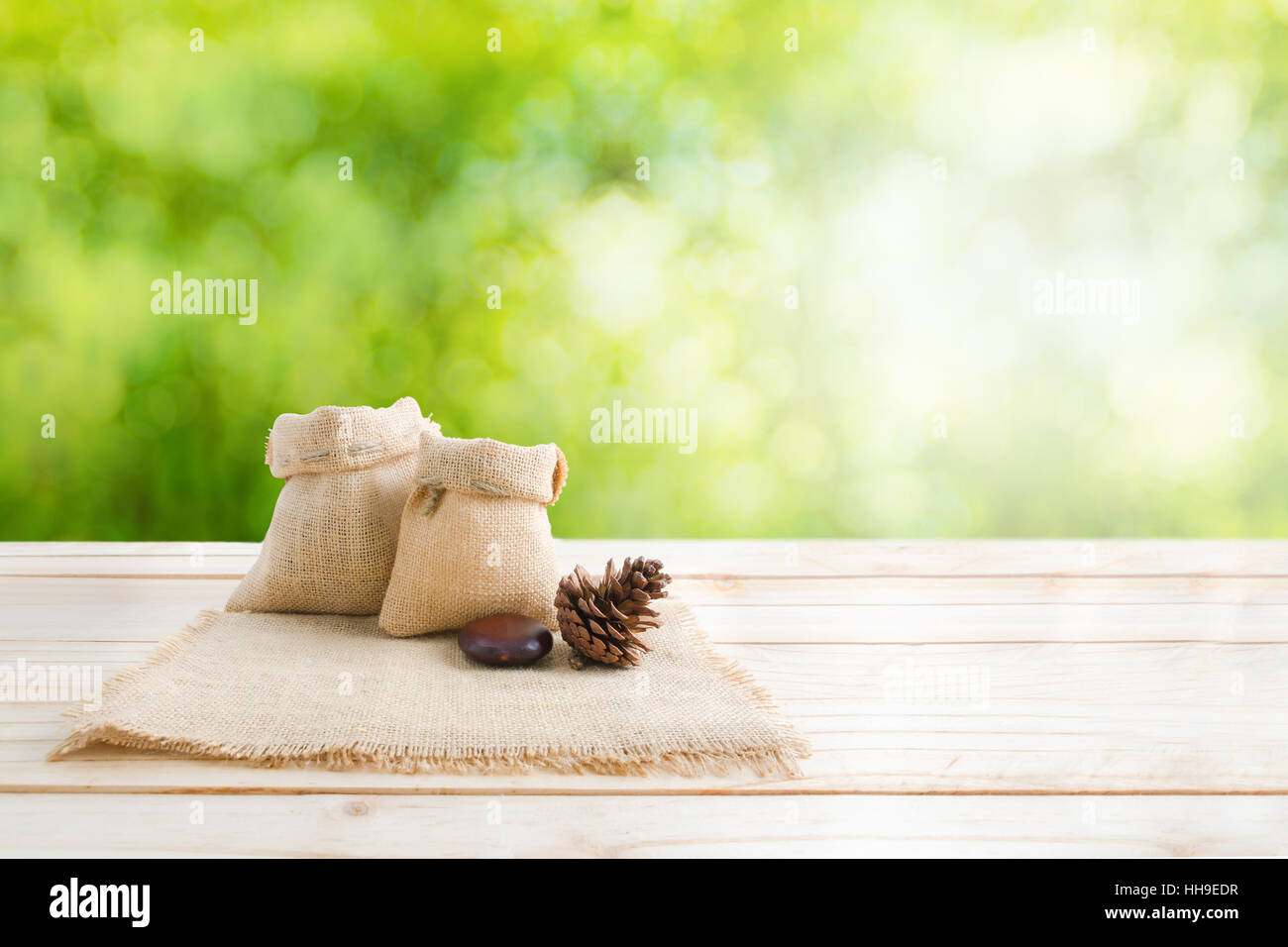 Merveilleux Two Of Blank Hemp Sack Bag And Pine Cones On Wood Table Top Floor Over Blur  Green Bokeh Background With Copy Space