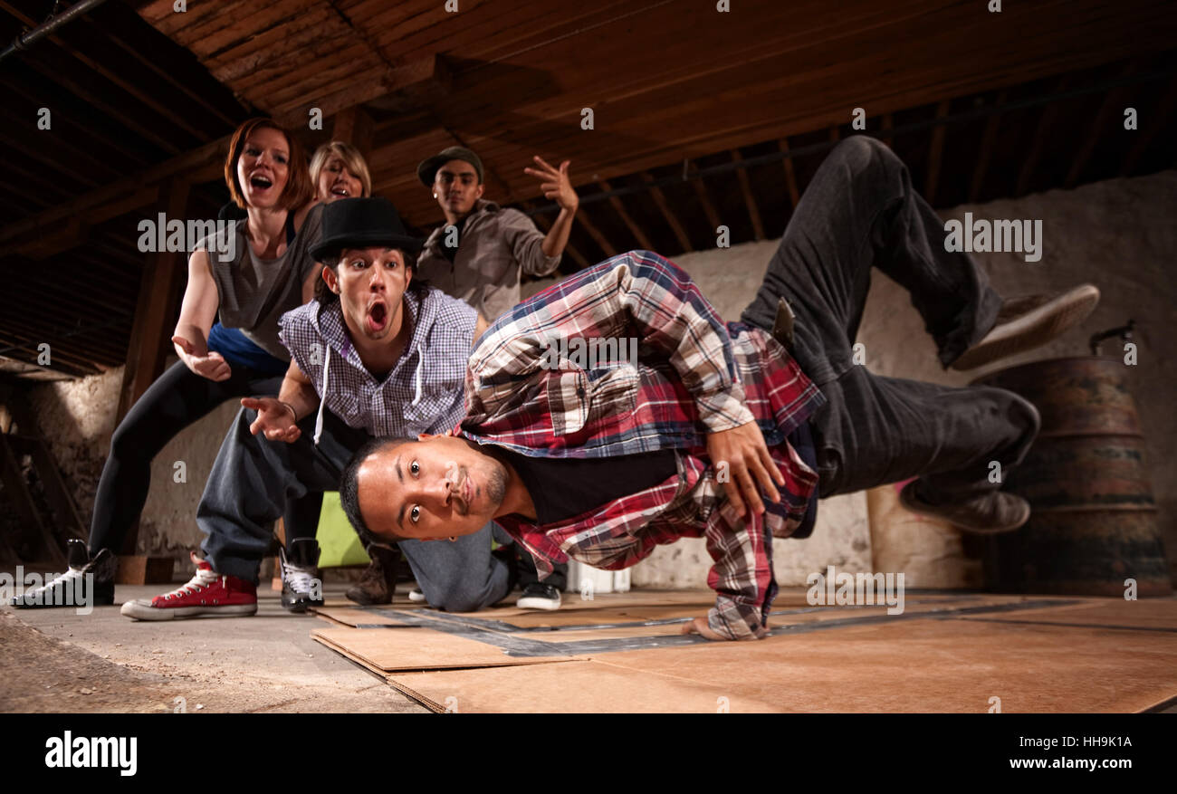 Young Asian man performs break dancing moves on cardboard Stock Photo