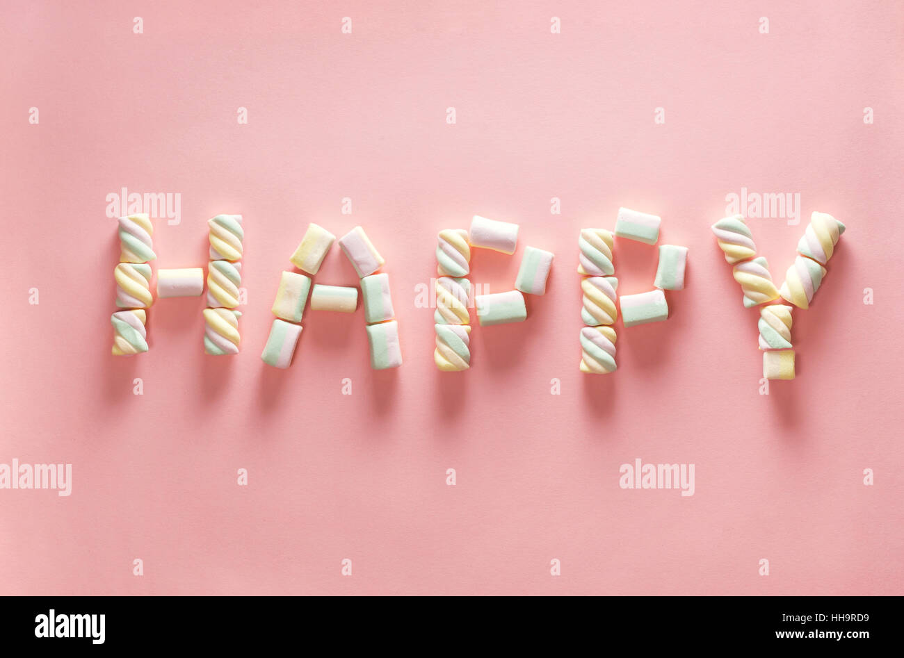 Letter HAPPY from marshmallow on gentle pink background. Flat lay. Image for valentine day concept - Stock Image