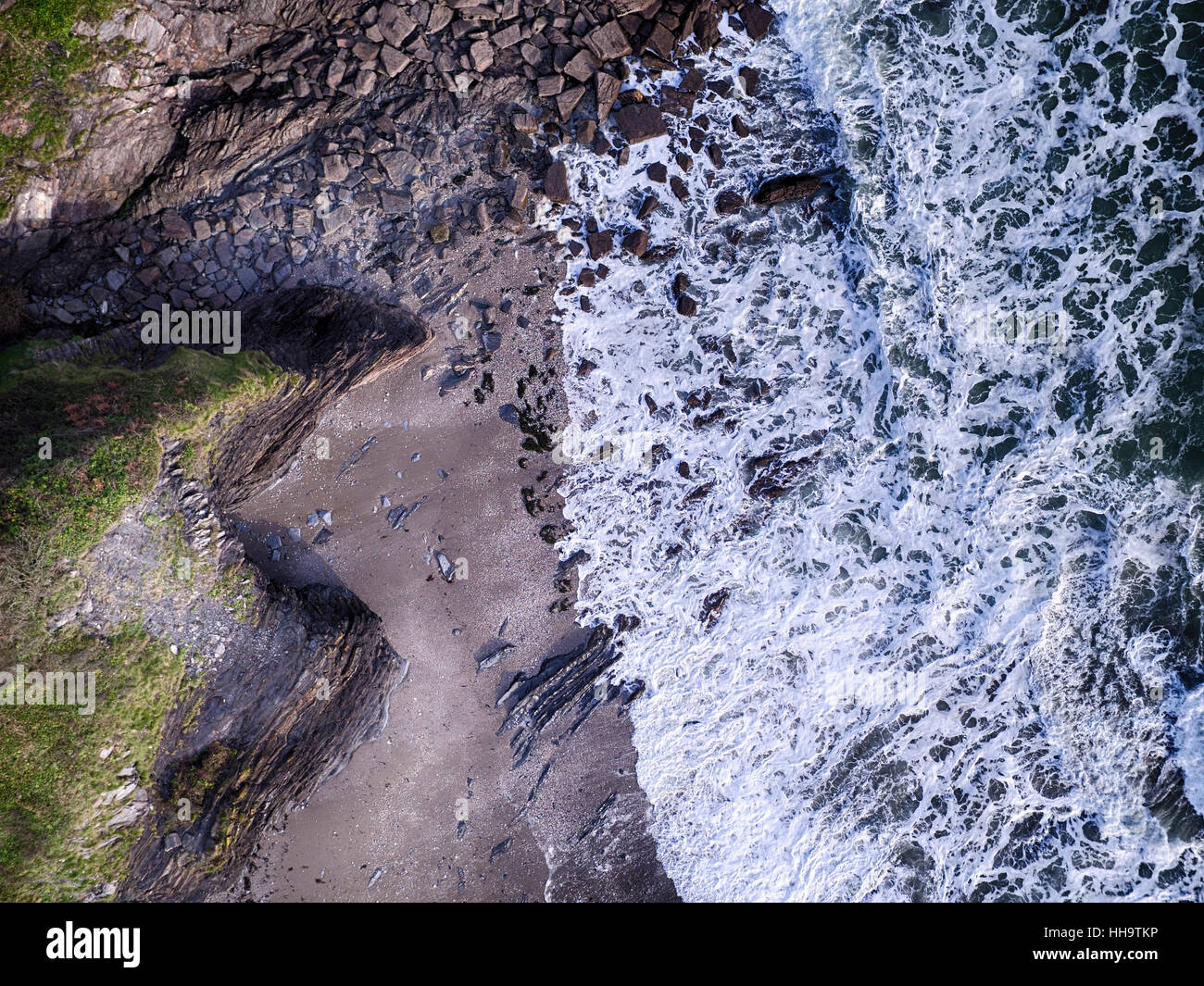 Cornwall beach with foaming waves crashing on rocks. Aerial photo - Stock Image