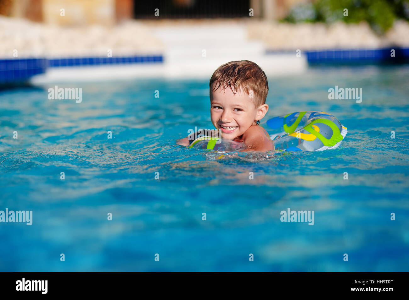 Happy little boy playing with colorful inflatable ring in outdoor swimming pool on hot summer day. Kids learn to - Stock Image