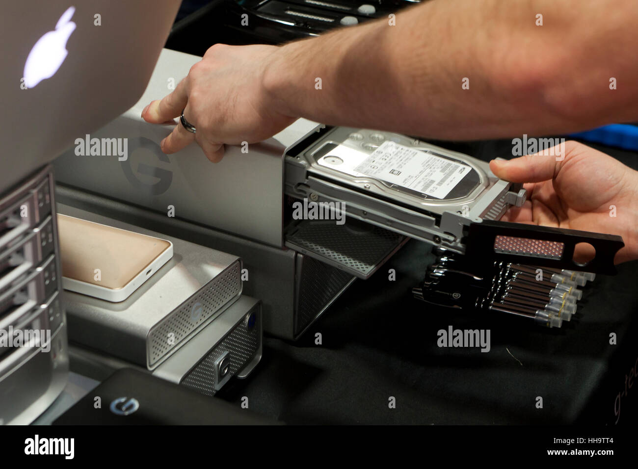 Man inserting hard drive into RAID Array - USA - Stock Image