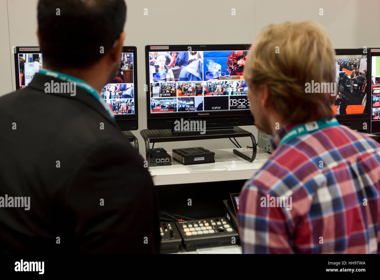 Video engineers in front of screens at tech expo - USA - Stock Image