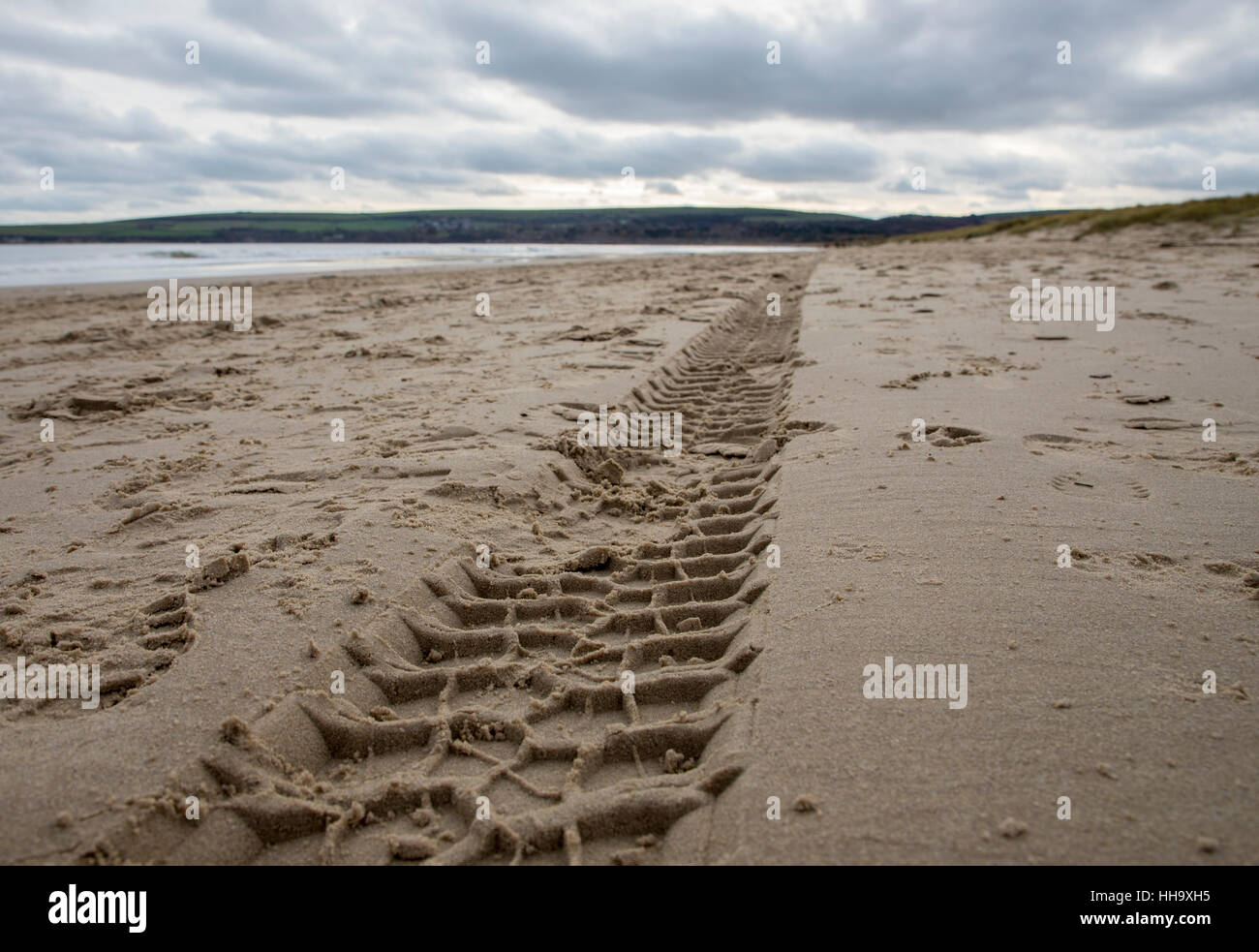 tyre mark tracks on sandy beach on grey day - Stock Image