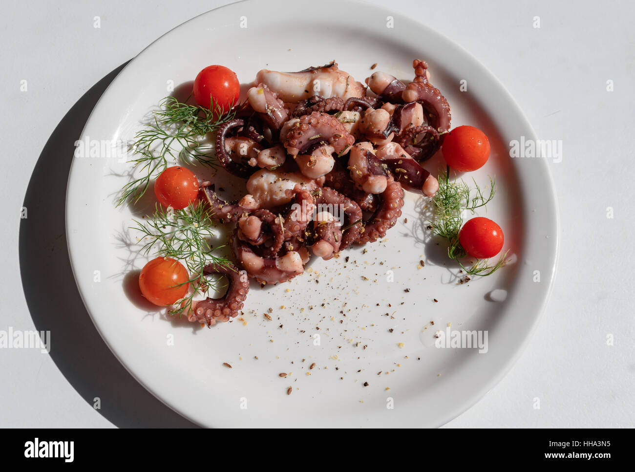 fried in olive oil, octopus tentacles with cherry tomatoes and spices served on white plate Stock Photo