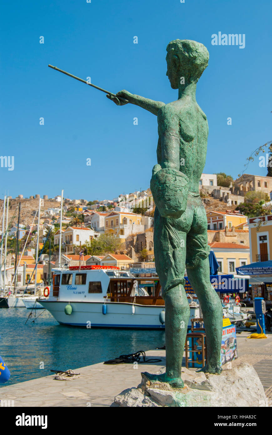 Statue of a young boy overlooking the harbour of Symi greece Stock ...