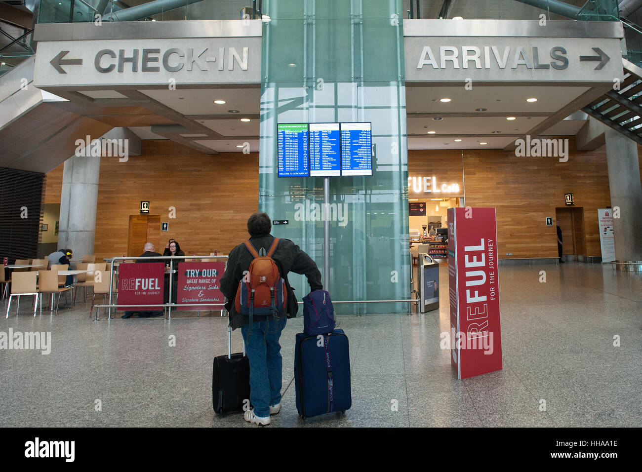 A passenger with luggage checks out the board at the departures terminal at Cork International Airport, Cork, Ireland - Stock Image