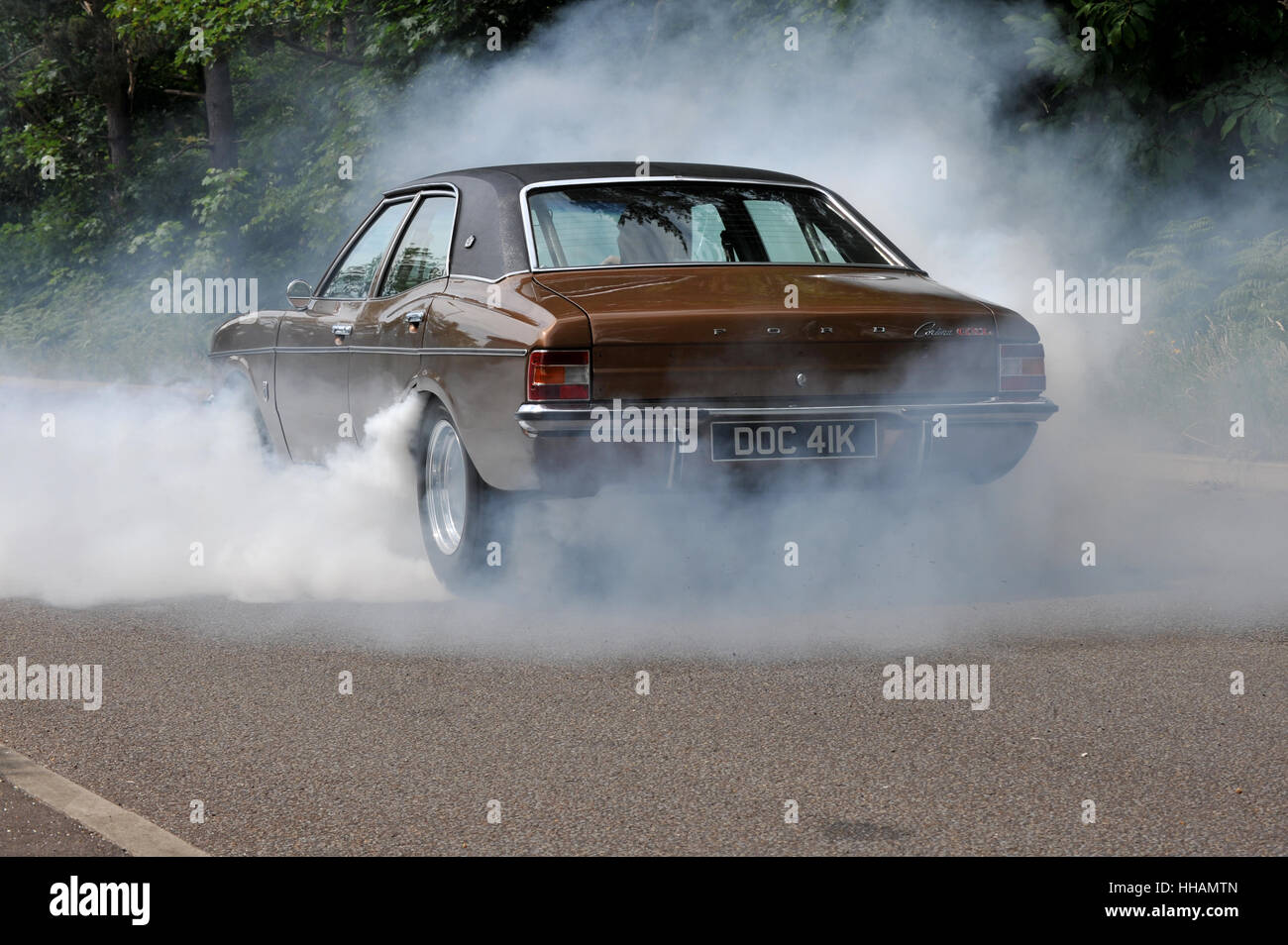 Tyre smoke from a burnout wheel spin by a 1972 Ford Cortina