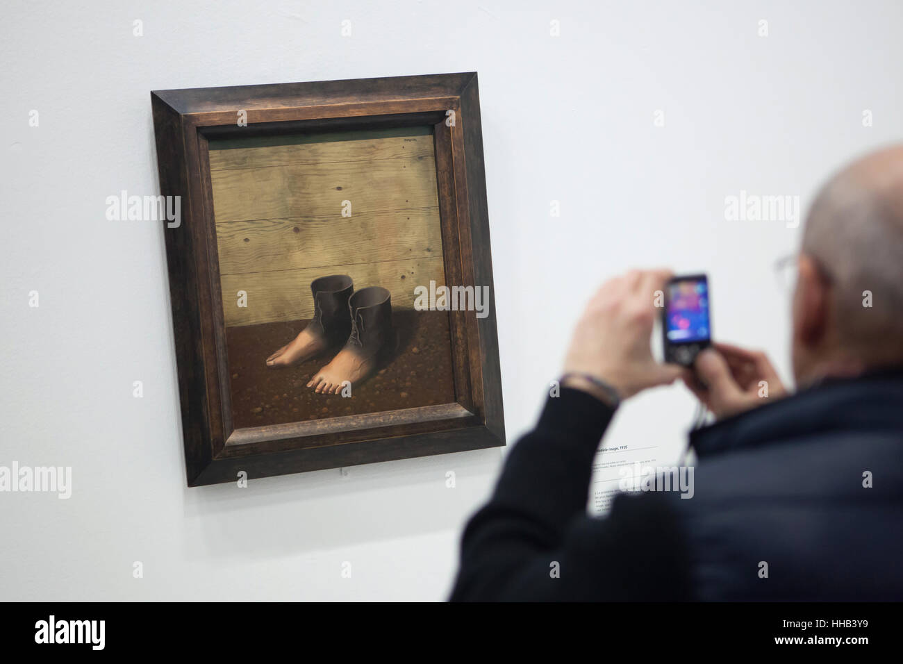 Visitor uses his smartphone to photograph the painting Le Modele Rouge (The Red Model, 1935) by Belgian surrealist - Stock Image