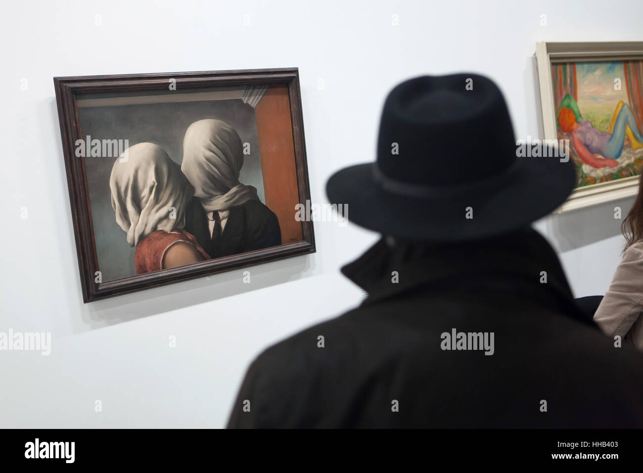 Visitor in front of the painting Les Amants (The Lovers, 1928) by Belgian surrealist artist Rene Magritte displayed - Stock Image