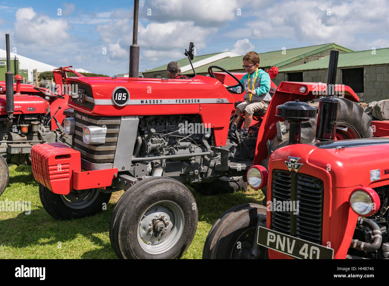 A young boy tries the wheel of a vintage Massey Ferguson 185 Tractor at  Anglesey Show