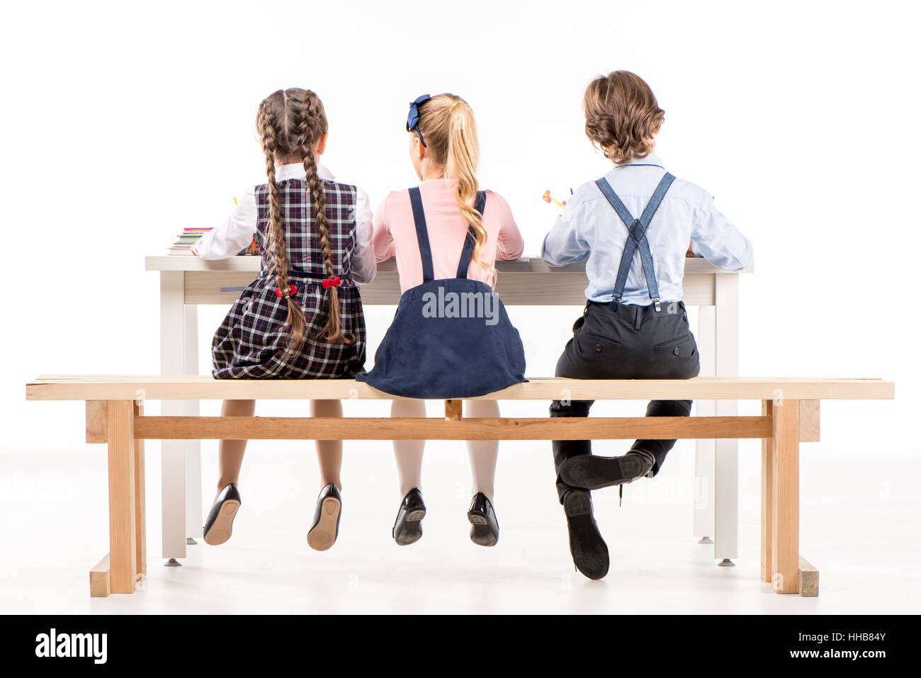 Back view of schoolchildren studying at desk on white - Stock Image