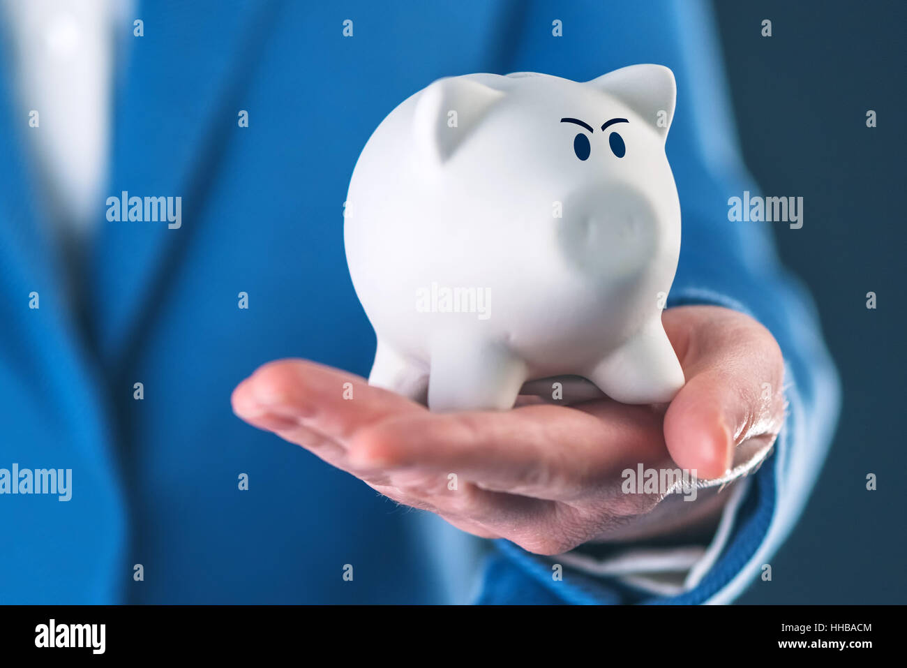 Angry piggy coin bank in businesswoman's hand, selective focus - Stock Image