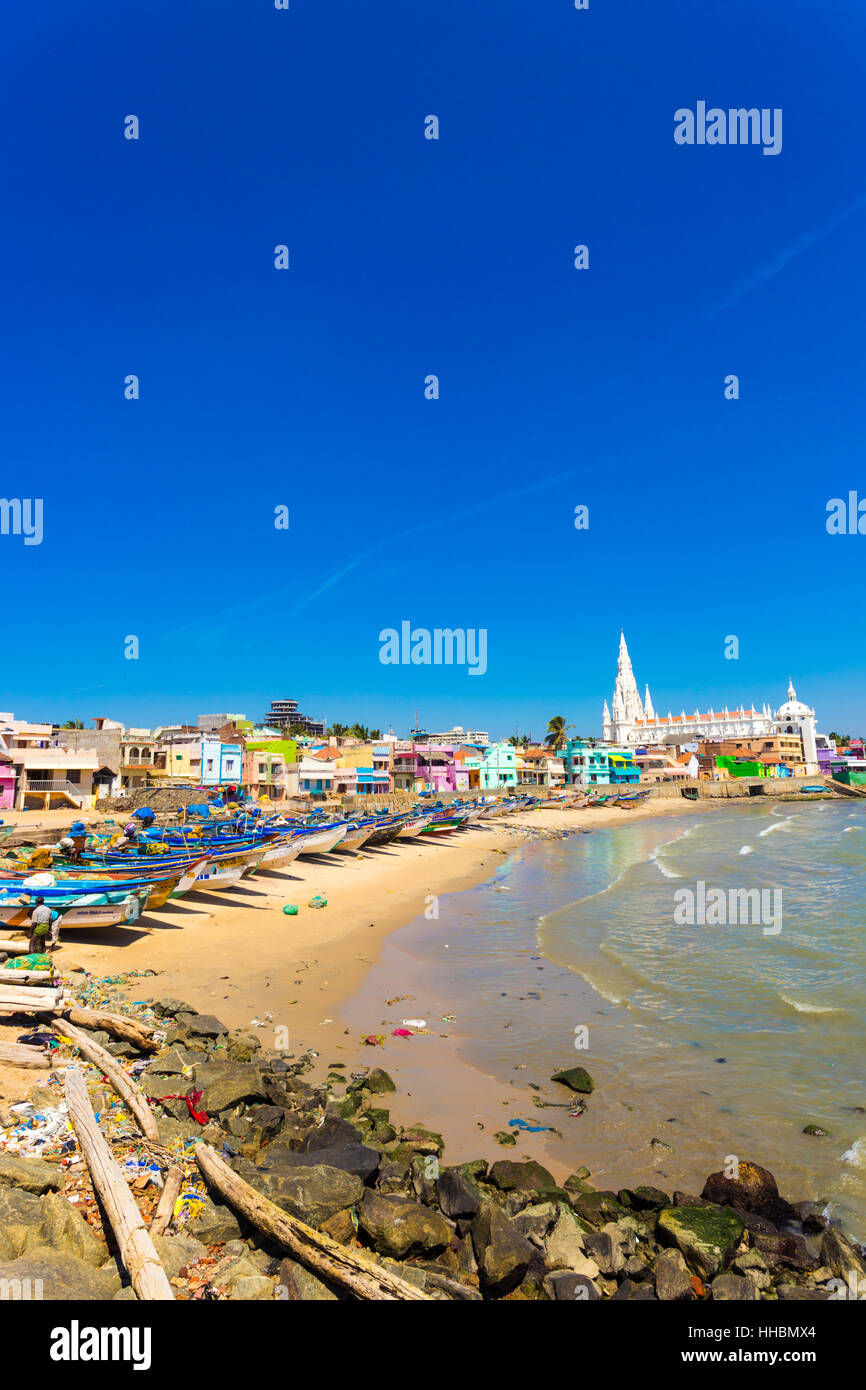 Our Lady of Ransom Shrine Church behind colorful houses on a sand beach occupied by fishing boats in Tamil Nadu. - Stock Image