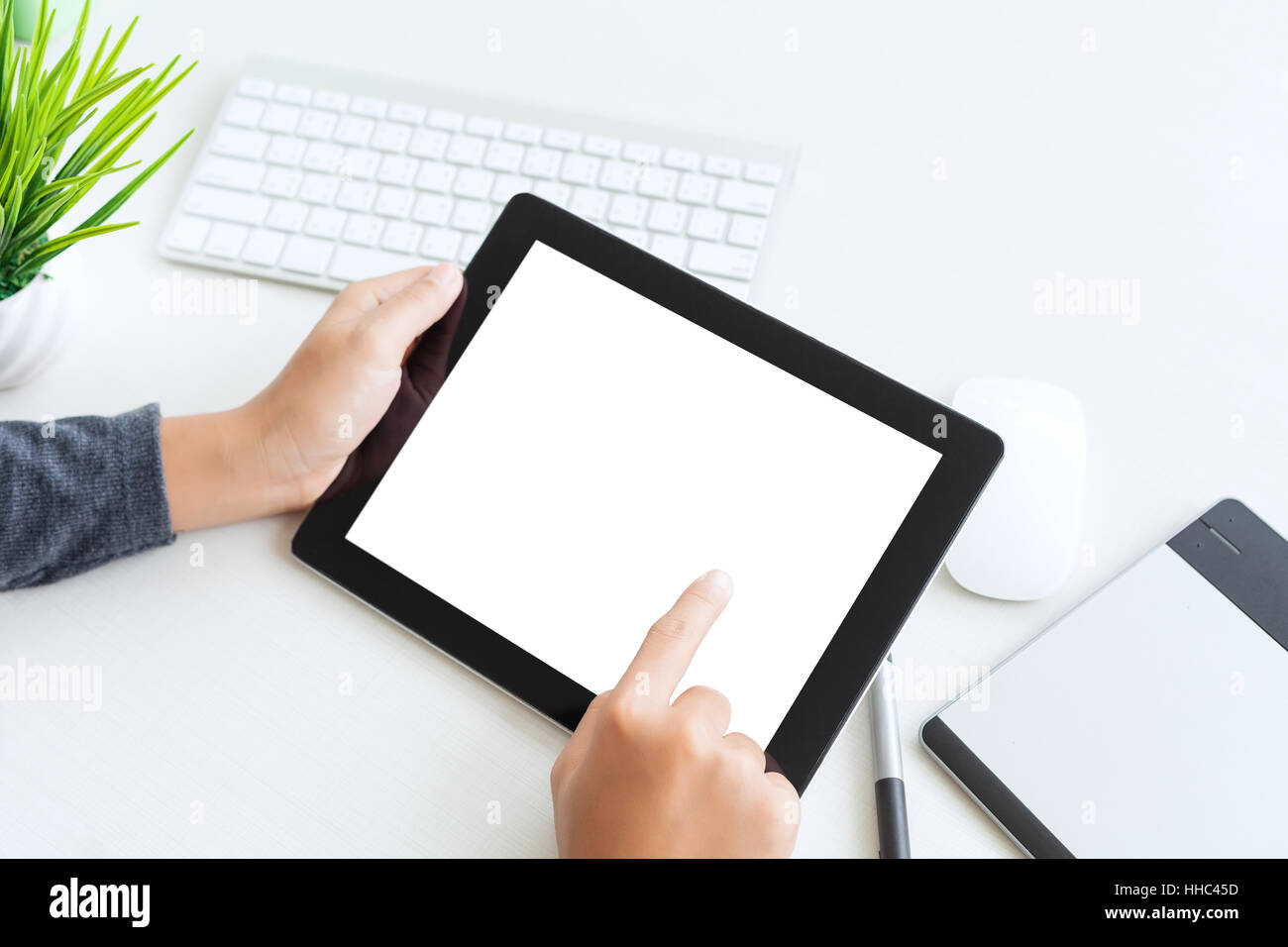 hand using digital tablet finger touch blank screen on desk work table Stock Photo