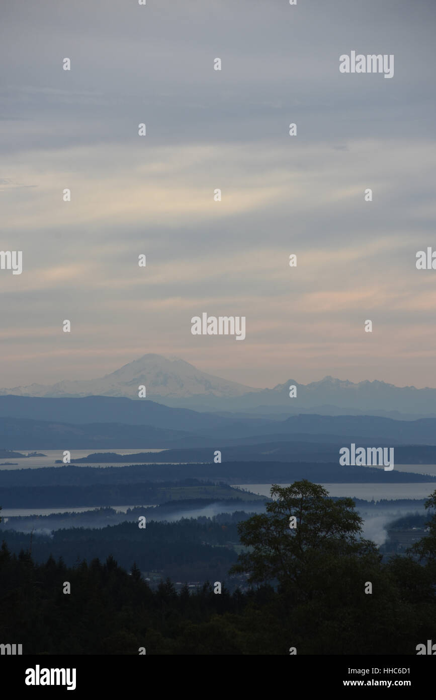 A view over hills and ocean on Vancouver Island, British Columbia, Canada looking to Mt. Baker in Washington State Stock Photo